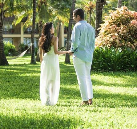 Couple walking in the grounds with Palm trees